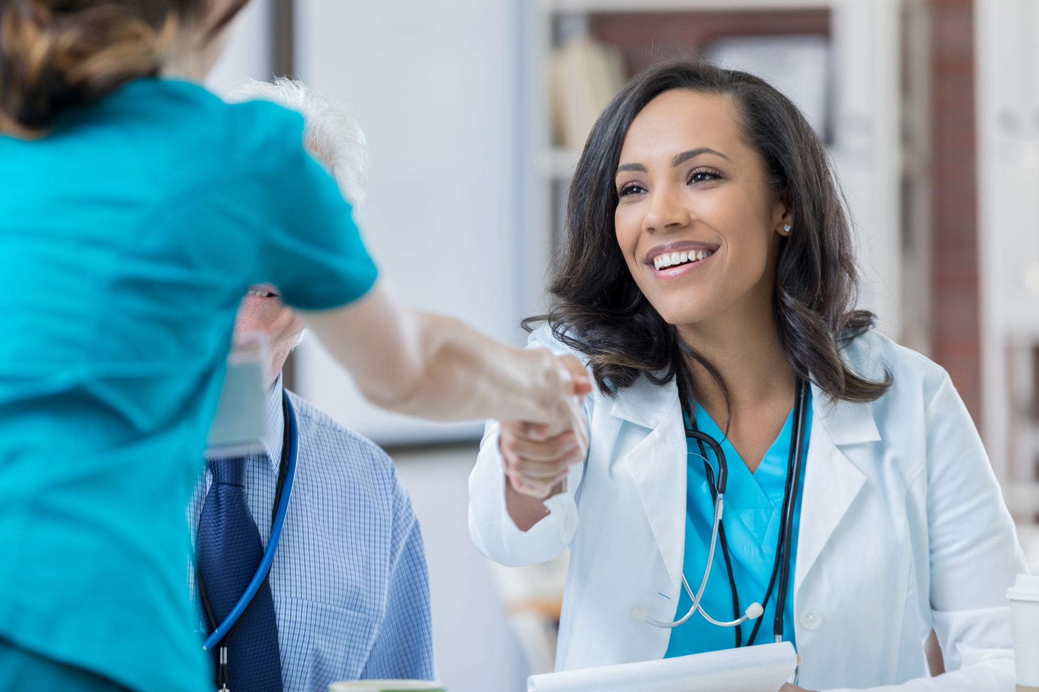 Beautiful mixed race doctor greets a nurse during job interview. The women are shaking hands.