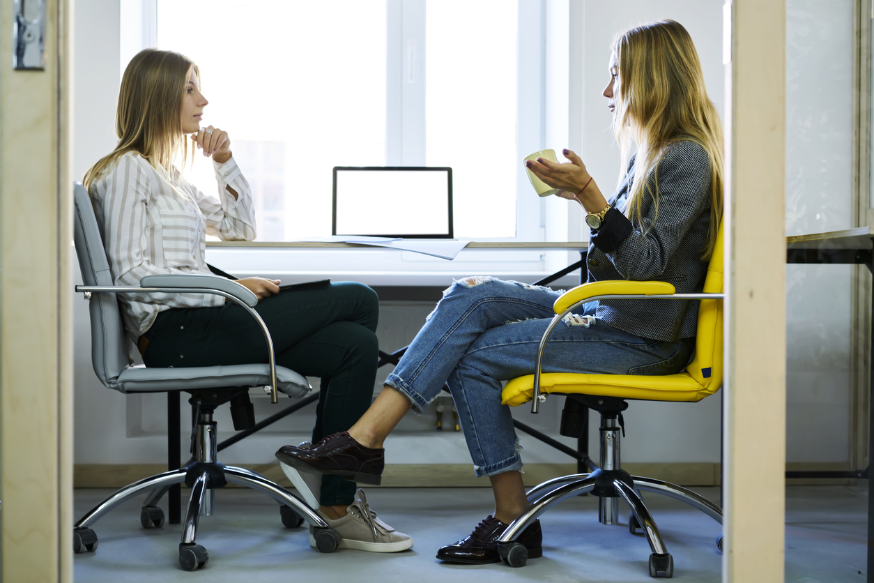Young female employee discussing working details with her administrative executive during informal meeting in coworking office sitting near modern laptop computer with mock up screen connected to wifi