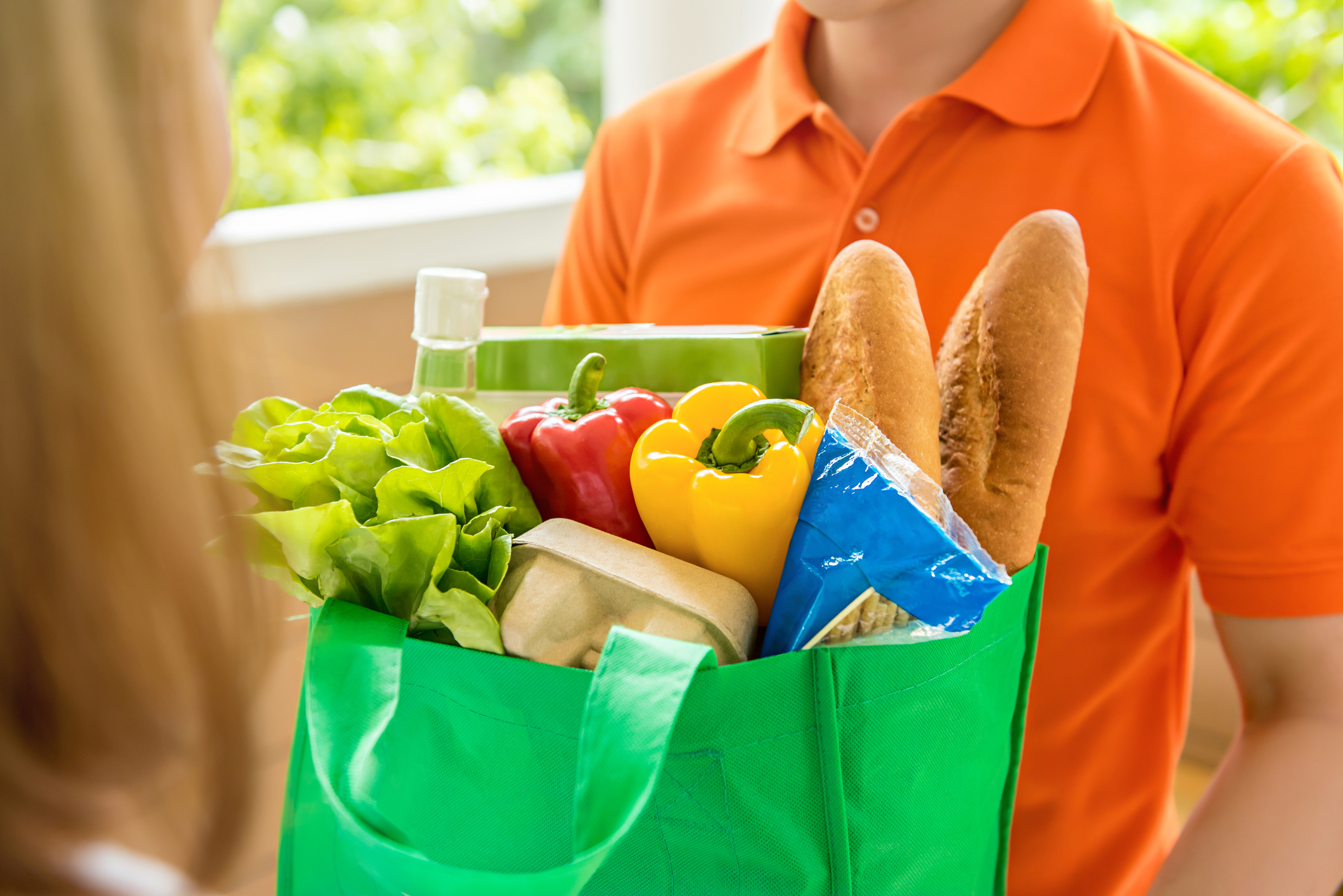Grocery store delivey man wearing orange polo-shirt delivering food to a woman at home